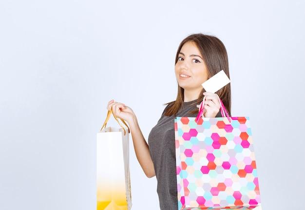 Ein modell der jungen frau, das einkaufstaschen trägt und ihre kreditkarte zeigt.