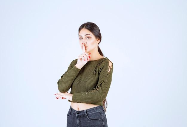 Ein modell der jungen frau, das stilles zeichen steht und tut.