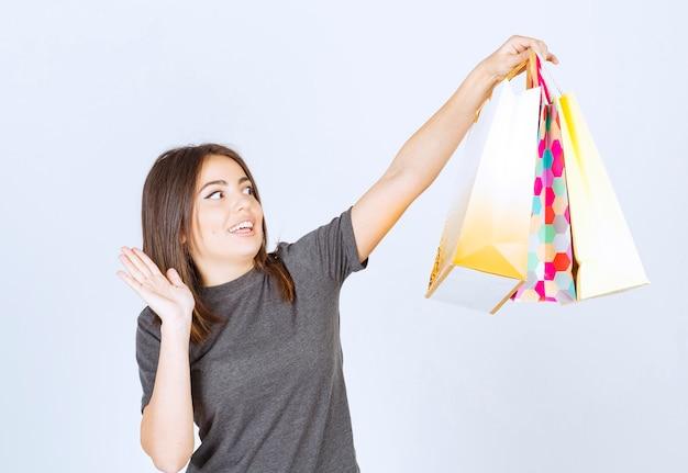 Ein modell der jungen frau, das viele einkaufstaschen auf weißem hintergrund hält.
