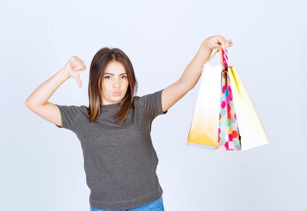Ein modell der jungen frau, das viele einkaufstaschen hält und einen daumen nach unten zeigt.
