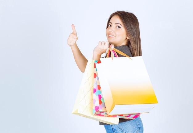 Ein modell der jungen frau, das viele einkaufstaschen hält und sich einen daumen zeigt.