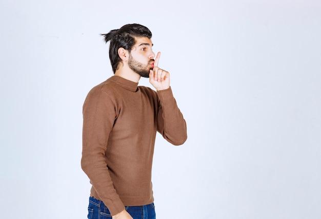 Ein modell des jungen mannes mit dem bart, der steht und stilles zeichen zeigt. foto in hoher qualität
