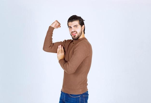 Ein modell des jungen netten mannes, das seinen bizeps über weißer wand steht und zeigt. foto in hoher qualität