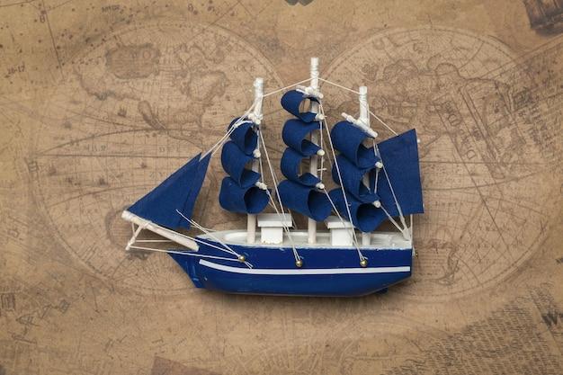 Ein modell eines segelboots mit blauen segeln über einer alten karte das konzept des reisens auf dem seeweg