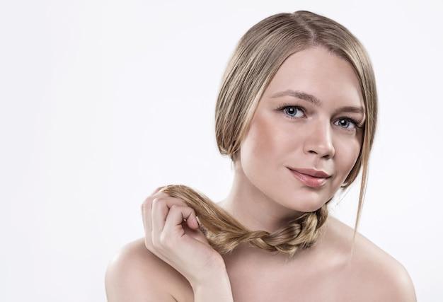 Ein modell mit blonden haaren, geflochten in einem zopf, heller haut, nackten schultern.