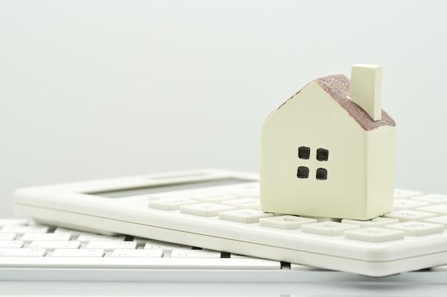 Ein modellhausmodell wird auf einen taschenrechner gelegt.