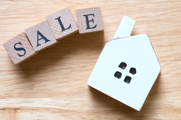 Ein modellhausmodell wird auf hölzernen wortverkauf gesetzt.
