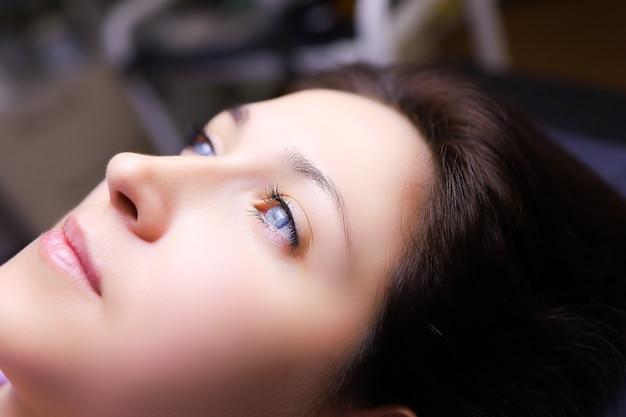 Ein modelmädchen mit blauen augen liegt auf einem permanent make-up verfahren ihre augenbrauen werden zum pudersprühen vorbereitet