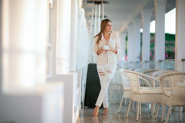 Ein modemodell-außenfoto der schönen frau mit blondem haar in eleganter kleidung.