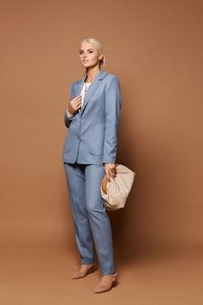 Ein modeporträt einer jungen geschäftsdame in einem eleganten blauen anzug, der mit stilvollem geldbeutel auf dem beigen hintergrund aufwirft. konzept der geschäftsmode und schönheit