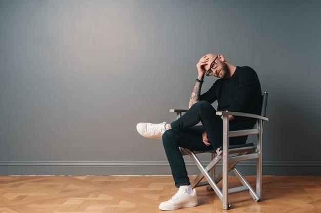 Ein moderner, stilvoller mann, der bein über bein sitzt