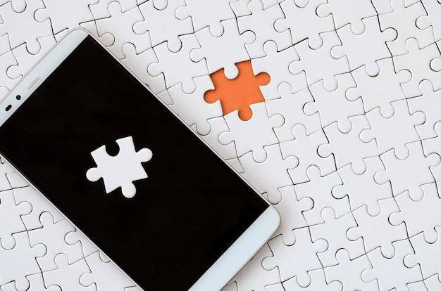 Ein modernes großes smartphone mit mehreren puzzle-elementen auf dem touchscreen liegt