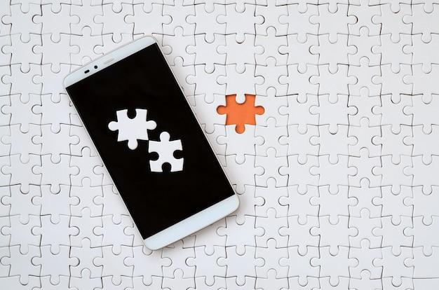 Ein modernes großes smartphone mit mehreren puzzleelementen auf dem touchscreen liegt auf weißem puzzle