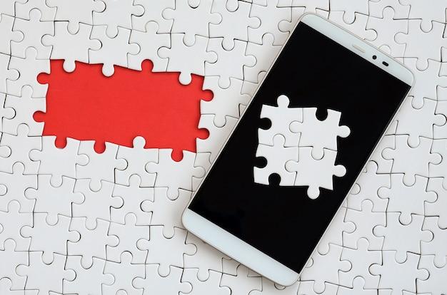 Ein modernes, großes smartphone mit mehreren puzzleelementen auf dem touchscreen liegt