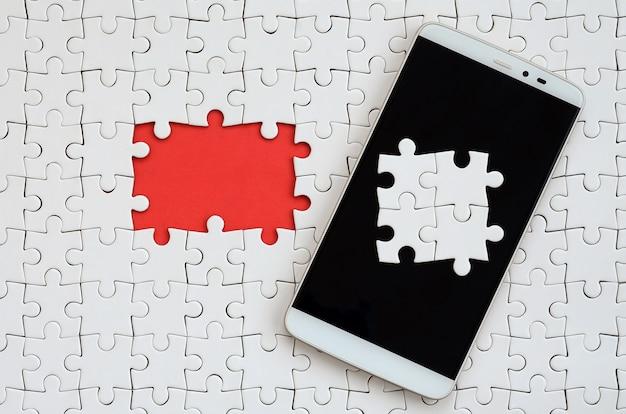 Ein modernes, großes smartphone mit mehreren puzzleelementen auf dem touchscreen
