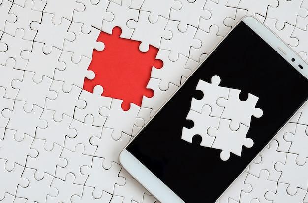 Ein modernes, großes smartphone mit mehreren puzzleteilen auf dem touchscreen liegt auf einem weißen puzzle
