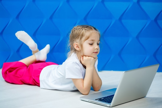 Ein modernes kindermädchen benutzt einen laptop, der auf dem boden liegt und die beine in die kamera schaut. lustiges kind auf einem hellblauen wandhintergrund. moderne internet-funktechnologie