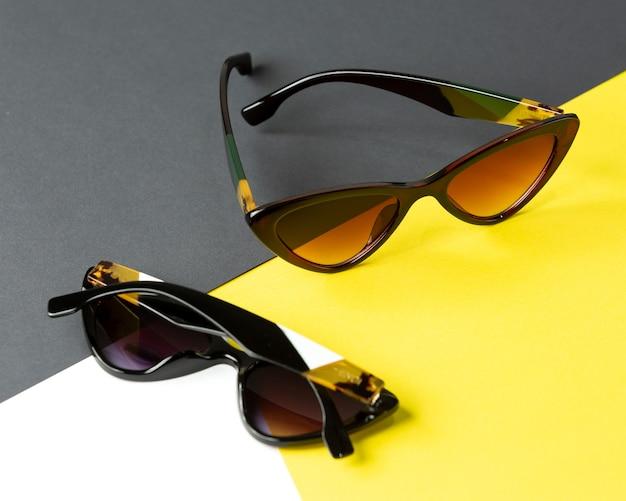 Ein modernes schwarzes sonnenbrillenpaar der draufsicht auf dem gelbschwarzen hintergrund isolierte die eleganz der sichtbrille