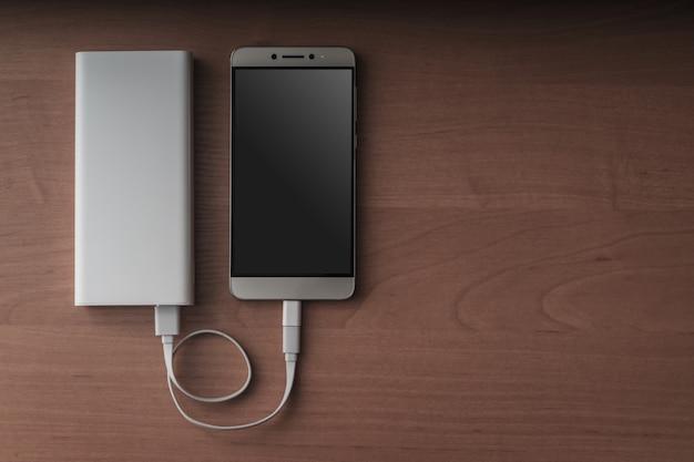 Ein modernes smartphone und eine angeschlossene energiebank