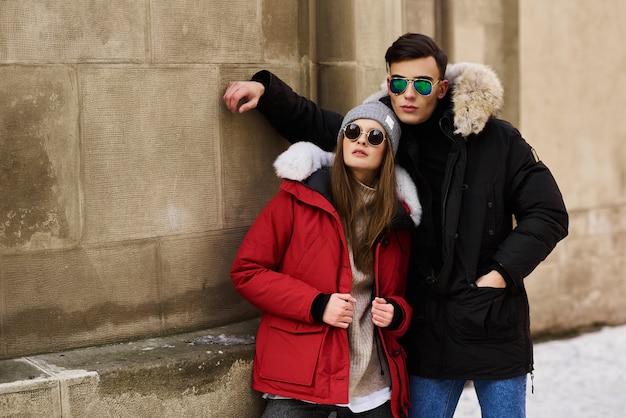 Ein modisches junges paar geht in die stadt zur weihnachtszeit