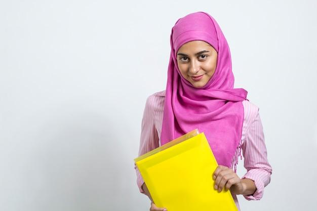 Ein moslemisches mädchen in einem hijab mit ordnern in ihren händen