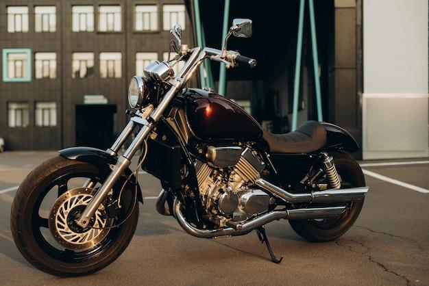 Ein motorrad auf einem parkplatz im warmen licht eines sonnenuntergangs. stilvolles custom chopper motorrad mit chromdetails. weicher selektiver fokus.