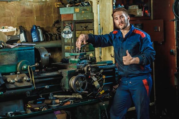 Ein müder arbeiter in einem blauen schutzanzug steht eine drehmaschine bereit.