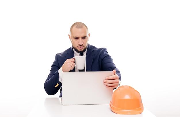 Ein müder bauunternehmer in einem orangefarbenen helm schaut auf den laptop-bildschirm und studiert das bauprojekt. sitzt am tisch und trinkt nervös kaffee