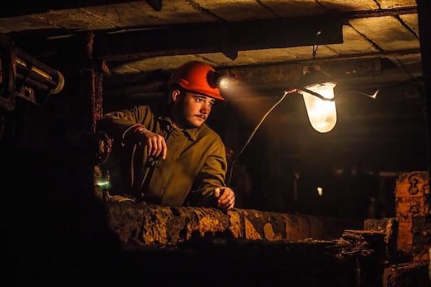 Ein müder bergmann in einer kohlengrube schaut ins licht. arbeit in einer kohlenmine.
