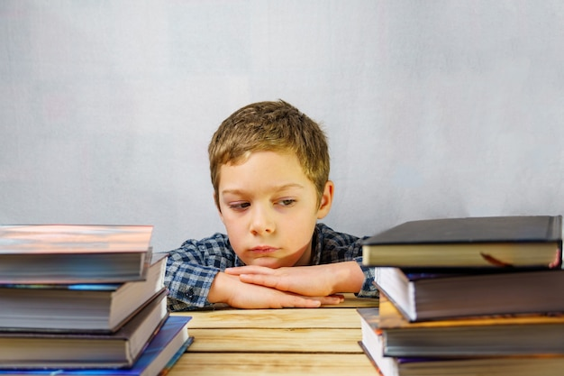 Ein müder, frustrierter schüler sitzt zwischen einem stapel bücher auf einem holztisch.