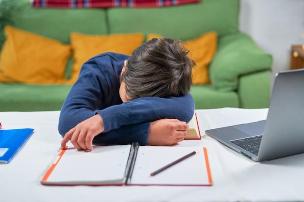 Ein müder schuljunge, der am schreibtisch schläft, während er hausaufgaben macht, innenraum