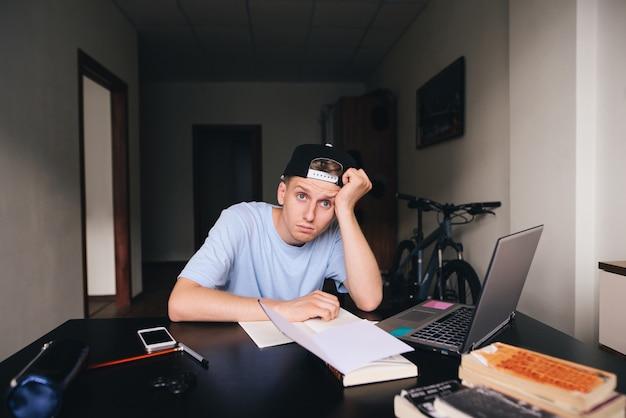 Ein müder student sitzt an seinem schreibtisch in seinem zimmer. hausaufgaben. ein blick in die kamera.