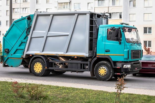 Ein müllwagen holt müll in einem wohngebiet ab. getrennte sammlung und entsorgung von müll. fahrzeug zur müllabfuhr.