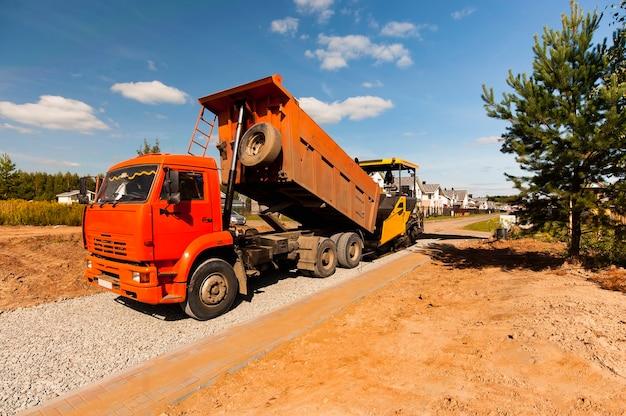 Ein muldenkipper entlädt heißen asphalt in einen asphaltfertiger, um im sommer eine neue straße zu bauen