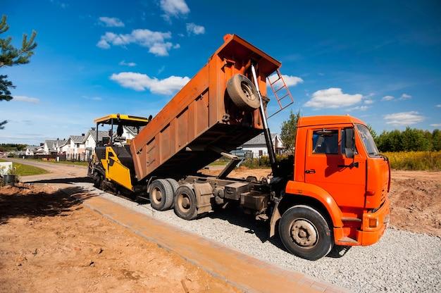 Ein muldenkipper entlädt heißen asphalt in einen asphaltfertiger, um im sommer in einem neuen dorf eine neue straße zu bauen