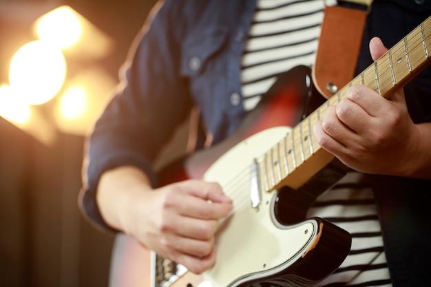 Ein musiker, der beim konzert e-gitarre spielt.