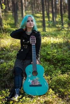 Ein musiker mit blauen haaren und einer blauen gitarre, der im park ruht.