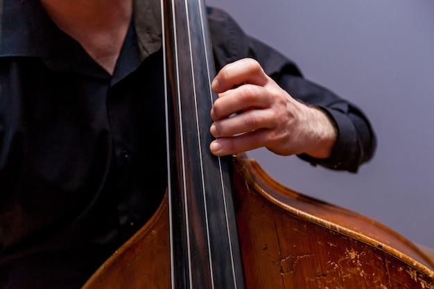 Ein musiker mit kontrabass in einem dunklen anzug, der auf dem hintergrund einer wand spielt.