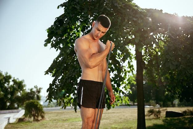 Ein muskulöser männlicher athlet, der training im park tut. gymnastik, training, fitness workout flexibilität. sommerstadt am sonnigen tag aktiver und gesunder lebensstil, jugend, bodybuilding.