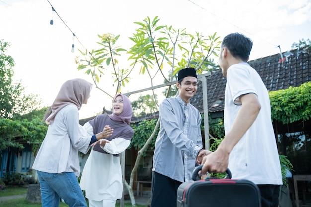 Ein muslimischer ehemann und eine muslimische ehefrau geben ihrer familie die hand, wenn sie sich treffen