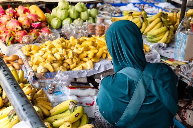 Ein muslimischer kaufmann verkauft eine vielzahl von früchten auf dem stall am lokalen markt in thailand