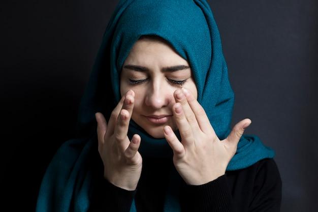 Ein muslimisches mädchen weint und wischt sich die tränen ab.