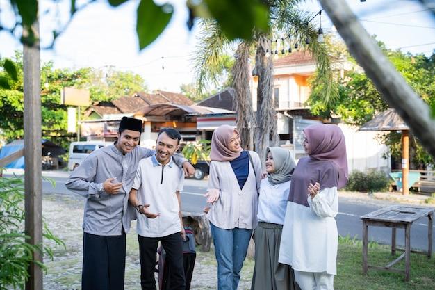 Ein muslimisches paar kam mit einem koffer, um von familienmitgliedern begrüßt zu werden