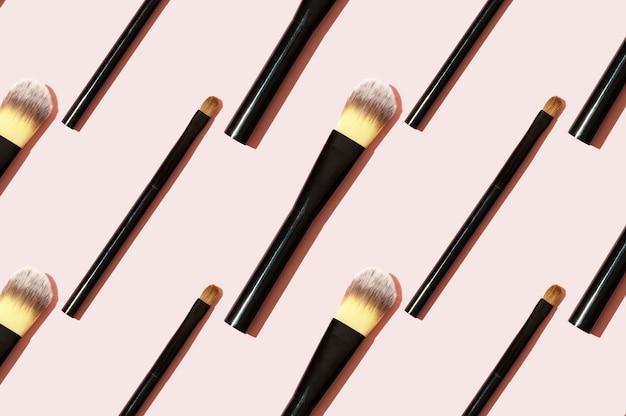 Ein muster aus schwarzen make-up-pinseln. moderner heller dekorativer hintergrund. damenaccessoires auf rosa hintergrund. professionelles makeup artist tool zum auftragen von lidschatten und foundation.