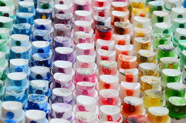 Ein muster aus vielen düsen eines farbspritzgeräts zum zeichnen von graffiti, verschmiert in verschiedenen farben. die kunststoffkappen sind in vielen reihen angeordnet und bilden die farbe des regenbogens