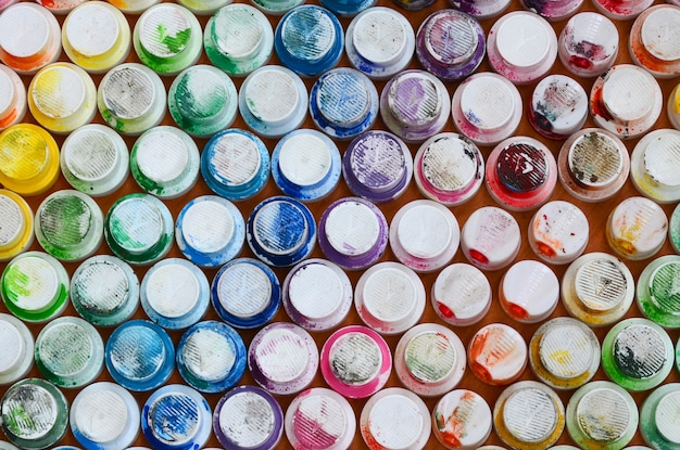 Ein muster aus vielen düsen eines farbspritzgeräts zum zeichnen von graffiti, verschmiert in verschiedenen farben.