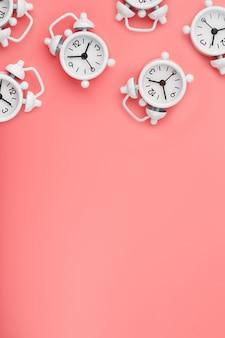 Ein muster vieler weißer klassischer wecker in form eines musters auf einem rosa hintergrund. draufsicht mit einer kopie des raumes, flach gelegen.