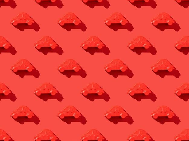 Ein muster von roten autos auf einer leuchtend roten oberfläche