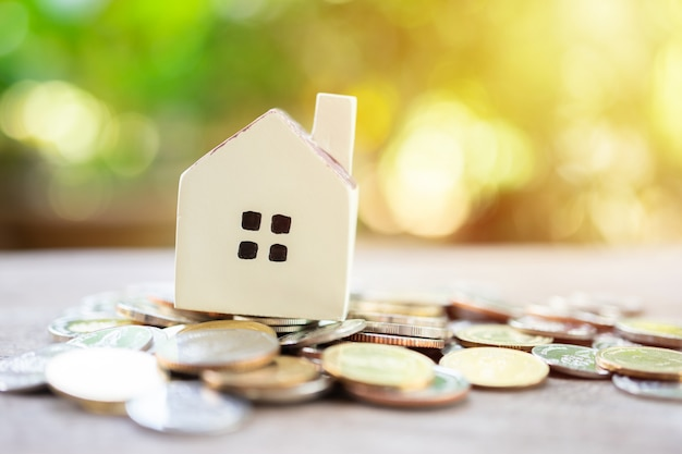 Ein musterhausmodell wird auf einen stapel münzen gelegt