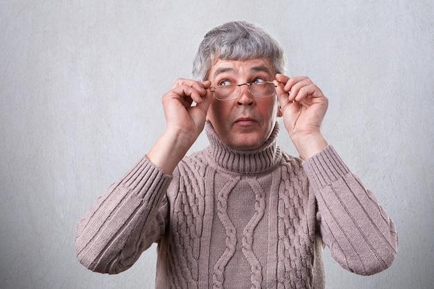 Ein mysteriöser älterer mann mit grauem haar, der brillen trägt, die beiseite schauen. kluger erwachsener berührt seine brille und denkt nach
